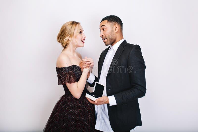逗人喜爱的夫妇的美好的愉快的片刻在爱的在白色背景 求婚,吃惊,圆环,礼物 库存图片