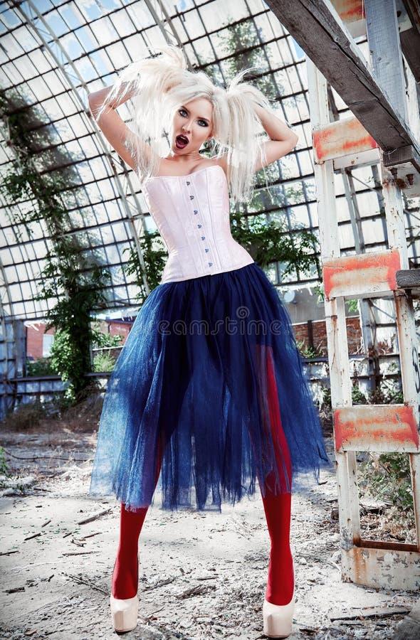 逗人喜爱的奇怪的离经叛道之人的女孩画象  穿着杂色的束腰、贴身衬衣和芭蕾舞短裙裙子的可爱的奇怪的妇女在被破坏的地方 奇怪的烦恼 库存照片