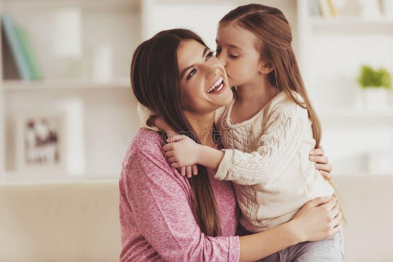 逗人喜爱的女儿亲吻了年轻母亲 图库摄影