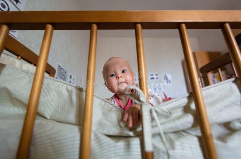 逗人喜爱的女婴画象有蓝眼睛的在小儿床坐 可爱的婴儿在轻便小床单独坐和感兴趣 库存图片