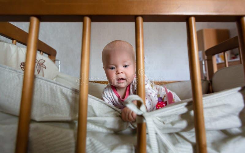 逗人喜爱的女婴画象有蓝眼睛的在小儿床坐 可爱的婴儿在轻便小床单独坐和感兴趣 免版税库存图片