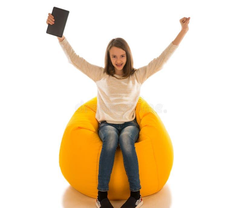 年轻逗人喜爱的女孩举起她的手和拿着片剂,当si时 库存照片
