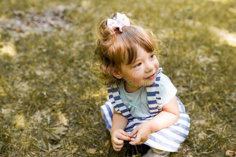 逗人喜爱的女孩使用与叶子在秋天公园 免版税库存图片