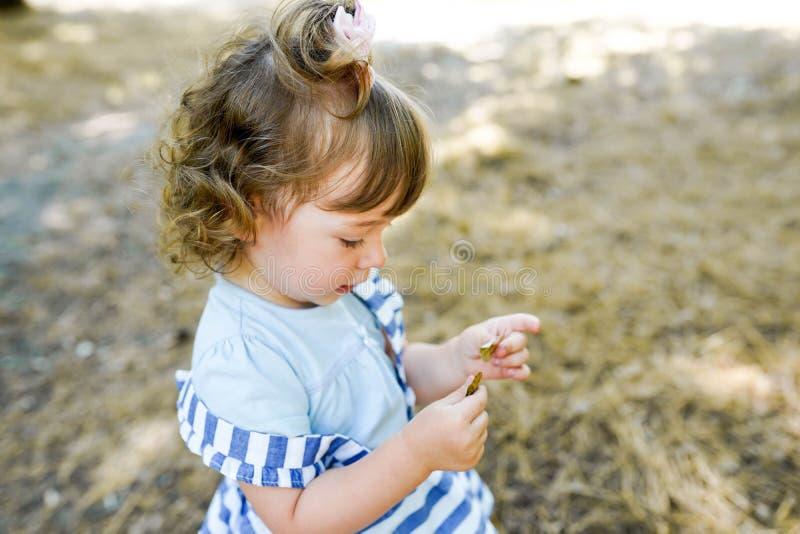 逗人喜爱的女孩使用与叶子在秋天公园 免版税库存照片
