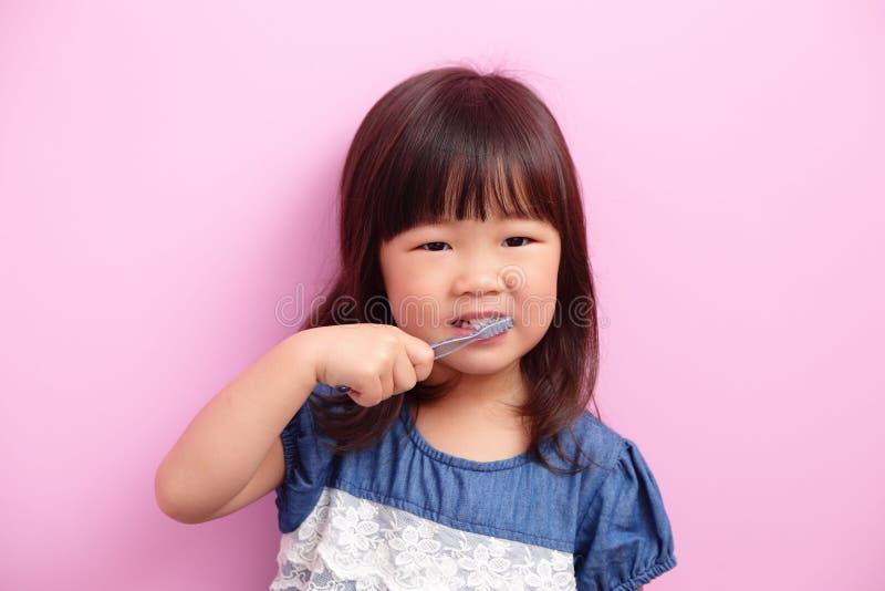 逗人喜爱的女孩刷子她的牙 免版税图库摄影