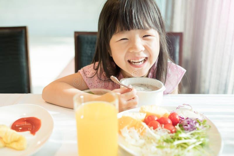 逗人喜爱的女孩吃早餐 免版税库存图片