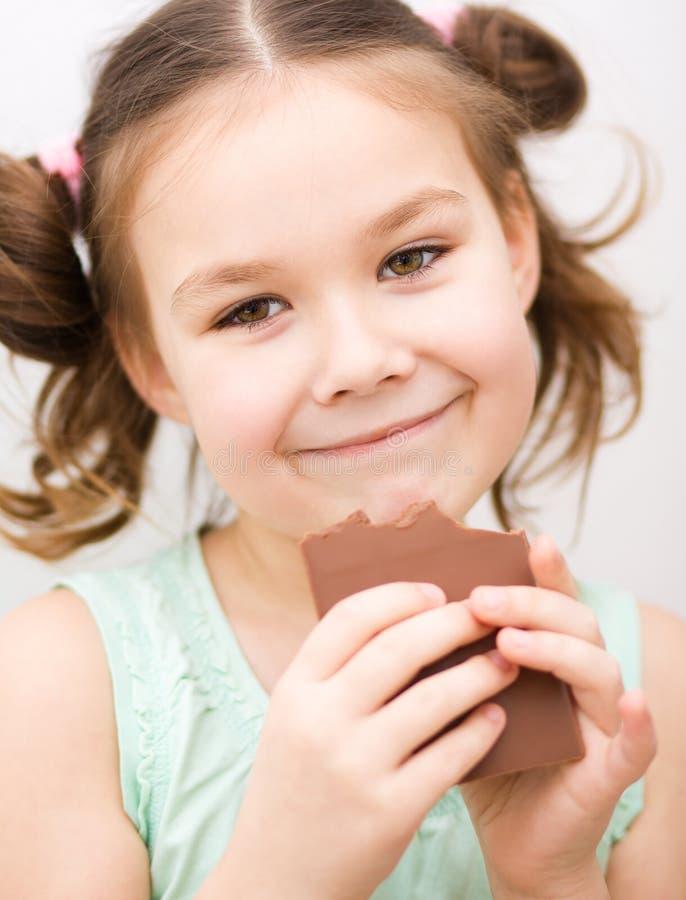 逗人喜爱的女孩吃着巧克力糖 免版税库存照片