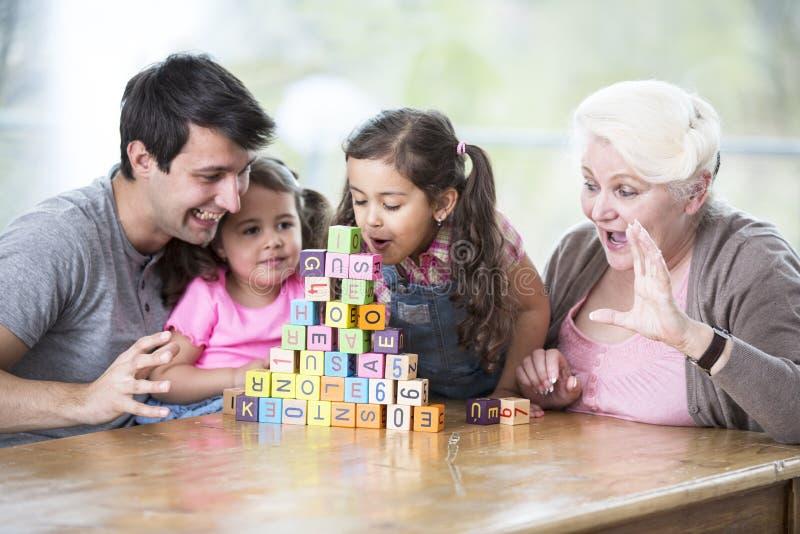 逗人喜爱的女孩吹的字母表块,当看它的家庭在房子里时 图库摄影