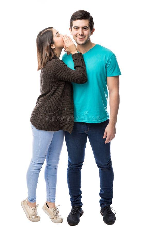 逗人喜爱的女孩告诉秘密对男朋友 免版税库存照片