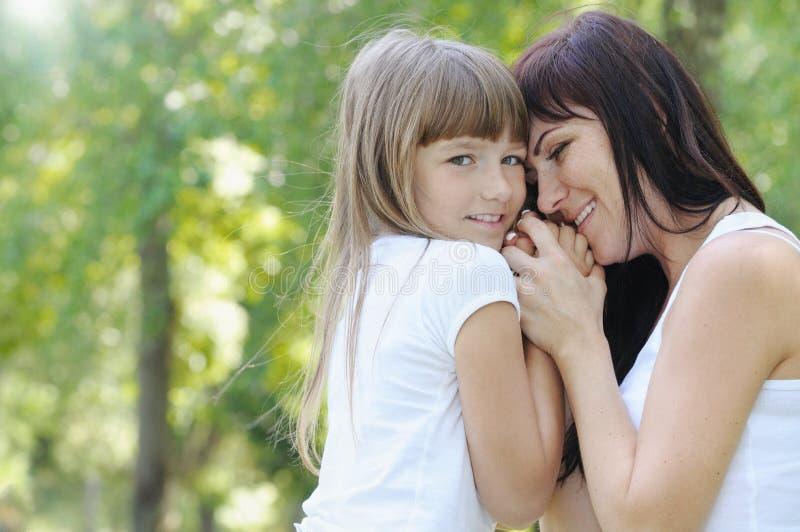 逗人喜爱的女孩和她的母亲嫩接触  库存图片