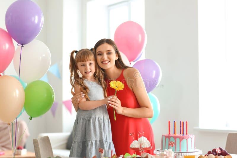 逗人喜爱的女孩和她的母亲有美丽的花的在生日宴会 免版税库存照片
