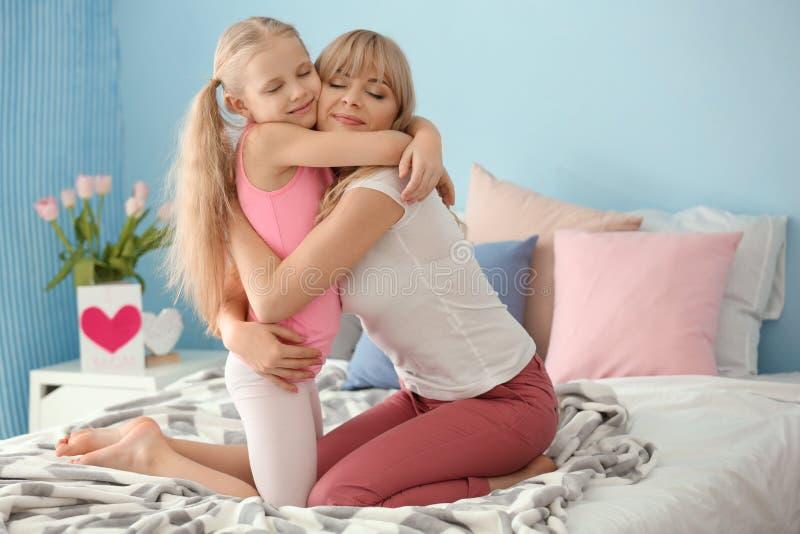 逗人喜爱的女孩和她的母亲画象在卧室 免版税库存照片