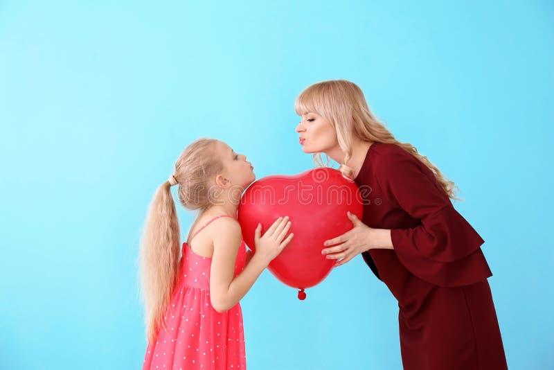 逗人喜爱的女孩和她的母亲画象有气球的在颜色背景 免版税图库摄影