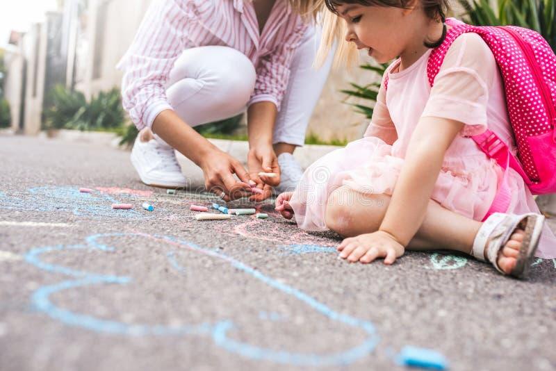 逗人喜爱的女孩和母亲图画的播种的图象与五颜六色的白垩的在边路 一起白种人白肤金发的女性戏剧 图库摄影