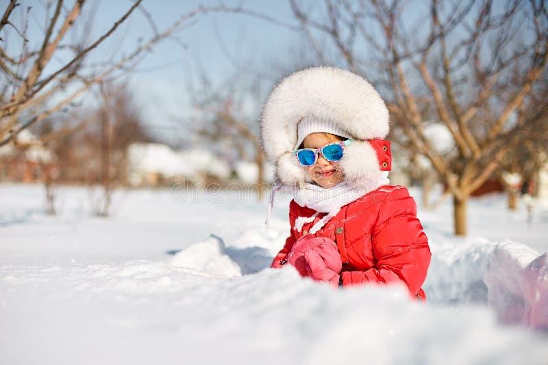 逗人喜爱的女孩在冬天,获得乐趣 库存照片