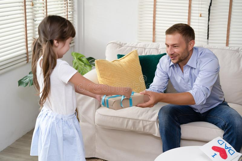 逗人喜爱的女孩在客厅在家给她的父亲礼物盒 愉快的父亲` s天 家庭假日,假期 库存照片