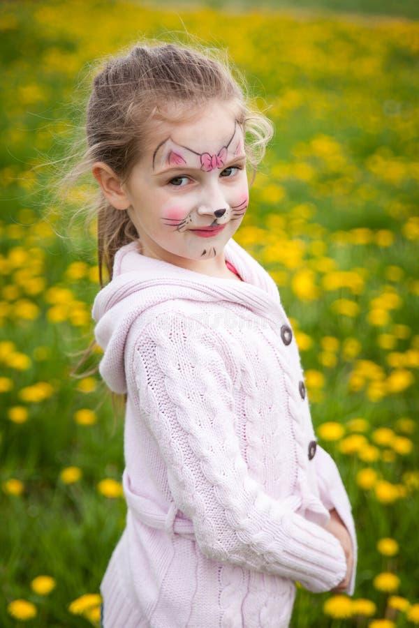 逗人喜爱的女孩在蒲公英草甸 免版税库存图片