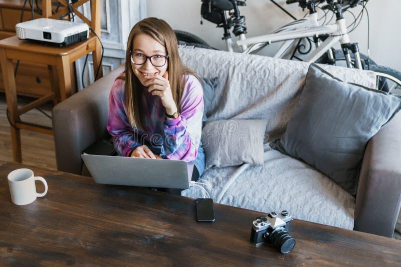 逗人喜爱的女孩坐在有玻璃的计算机并且看照相机并且谨慎地微笑 计算机例证向量妇女 库存照片