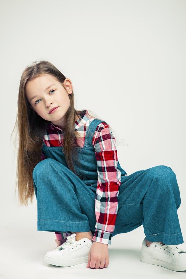 逗人喜爱的女孩坐地板 在一套牛仔布衣服的孩子,在格子衬衫和白色运动鞋 演播室时尚摄影 ?? 库存图片