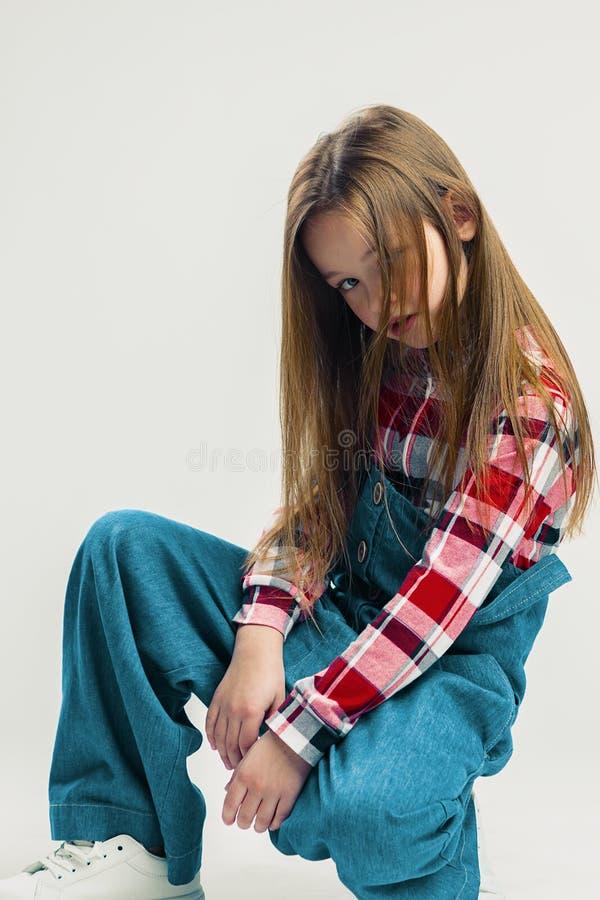 逗人喜爱的女孩坐地板 在一套牛仔布衣服的孩子,在格子衬衫和白色运动鞋 演播室时尚摄影 ?? 库存照片