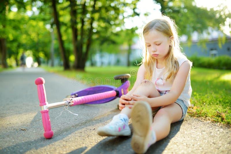 逗人喜爱的女孩坐地面在落她的滑行车在夏天公园以后 受到伤害的孩子,当乘坐反撞力时 免版税库存图片
