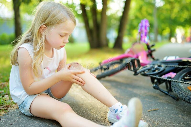 逗人喜爱的女孩坐地面在落她的自行车在夏天公园以后 受到伤害的孩子,当骑自行车时 图库摄影