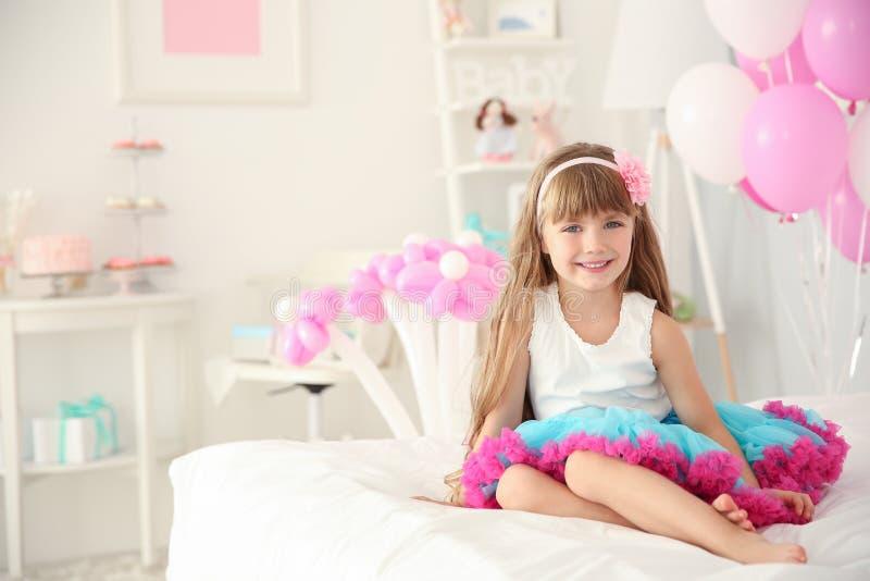 逗人喜爱的女孩坐床在为生日庆祝装饰的屋子里 免版税库存图片