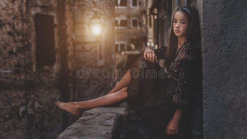 逗人喜爱的女孩坐老镇的屋顶 好女孩在中世纪城市 免版税库存图片