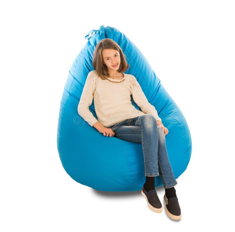 年轻逗人喜爱的女孩坐蓝色装豆子小布袋 库存照片