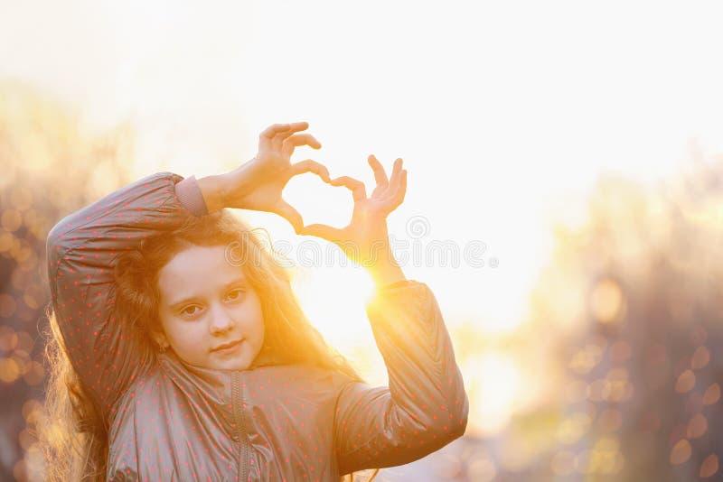 逗人喜爱的女孩女孩折叠了她的手心脏形式 免版税库存照片