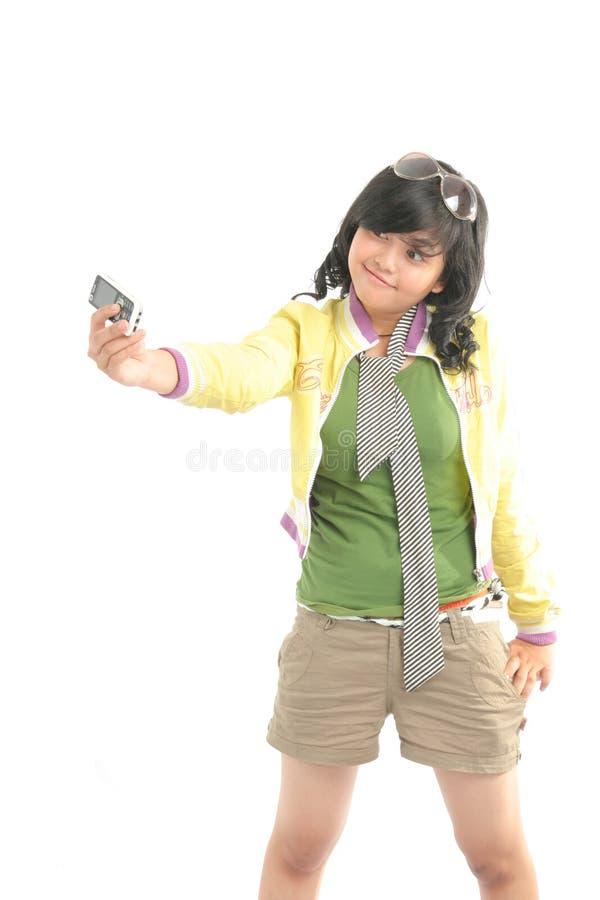 逗人喜爱的女孩她的照片自 免版税库存照片