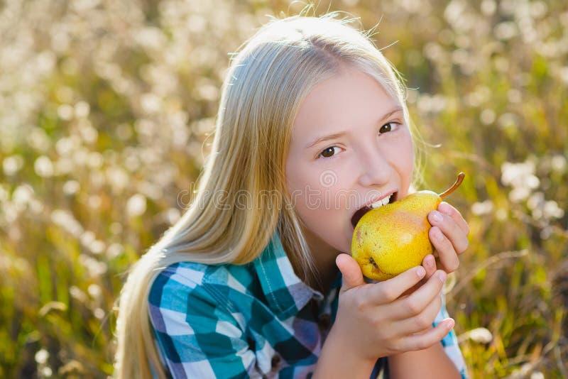 逗人喜爱的女孩或少年室外被吃的健康和水多的梨 库存图片