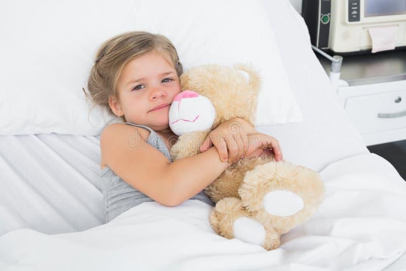 逗人喜爱的女孩拥抱玩具熊在医院病床上 库存照片