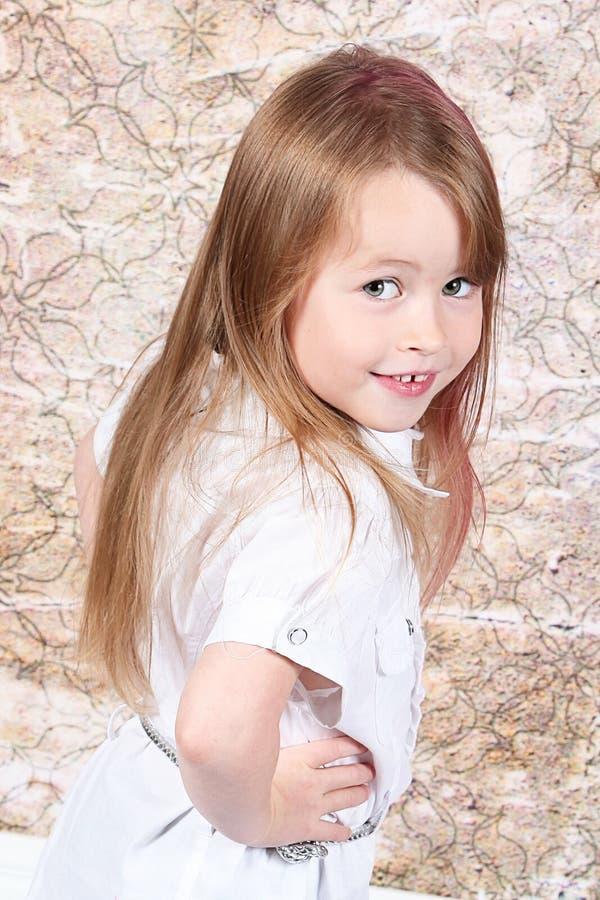 逗人喜爱的女孩摆在的一点 库存照片
