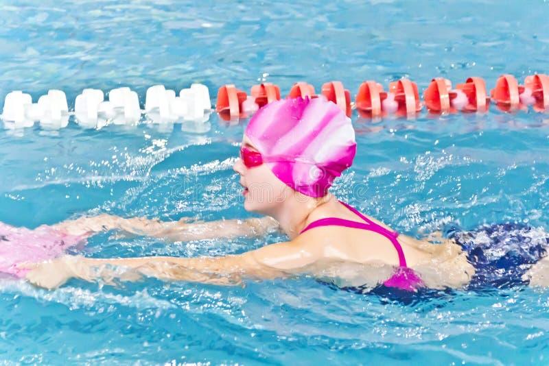 逗人喜爱的女孩池游泳 图库摄影
