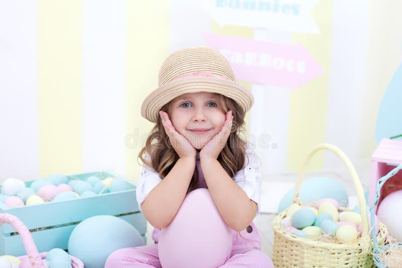 逗人喜爱的女孩特写镜头画象一个帽子的在复活节装饰背景 复活节彩蛋的逗人喜爱的女孩狩猎 复活节和春天déco 免版税库存图片