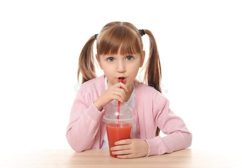 逗人喜爱的女孩用坐在桌上的柑橘汁反对白色背景 库存照片