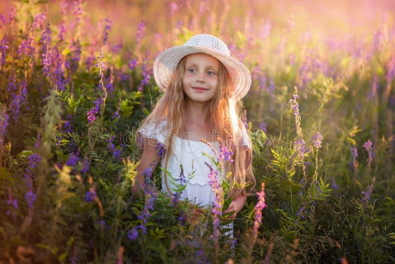 逗人喜爱的女孩画象有长的头发的在日落的一个帽子 库存图片