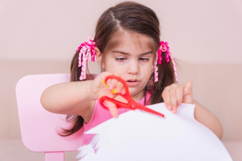 逗人喜爱的女孩裁减纸画象与的红色剪刀 免版税库存照片