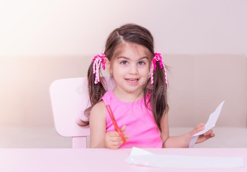 逗人喜爱的女孩裁减纸画象与的红色剪刀 库存照片