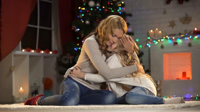 逗人喜爱的女孩错过的父亲和拥抱妈妈,坐在美丽的X-mas树附近 库存图片