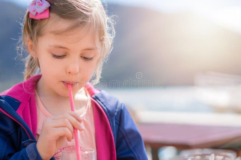 逗人喜爱的女孩饮用的汁液在夏天 图库摄影