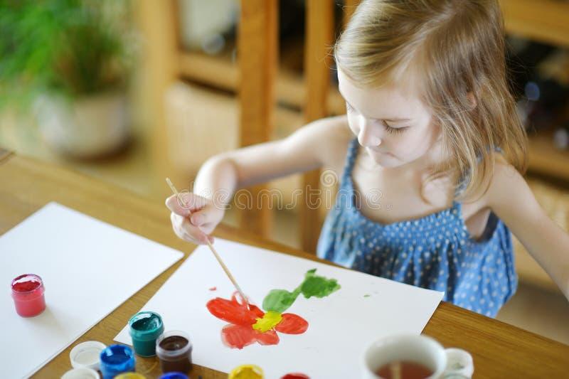 逗人喜爱的女孩画与在幼儿园的油漆 库存照片
