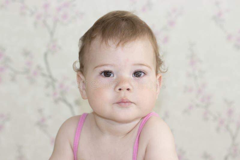 逗人喜爱的女孩10个月,婴孩画象特写镜头 婴孩看与一张严肃的面孔的照相机,女婴与 库存图片