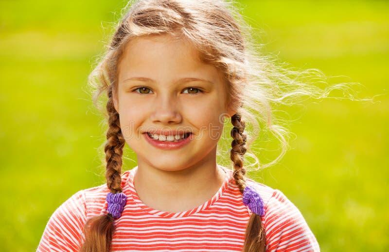 逗人喜爱的女孩画象有两条辫子的在夏天 免版税库存照片