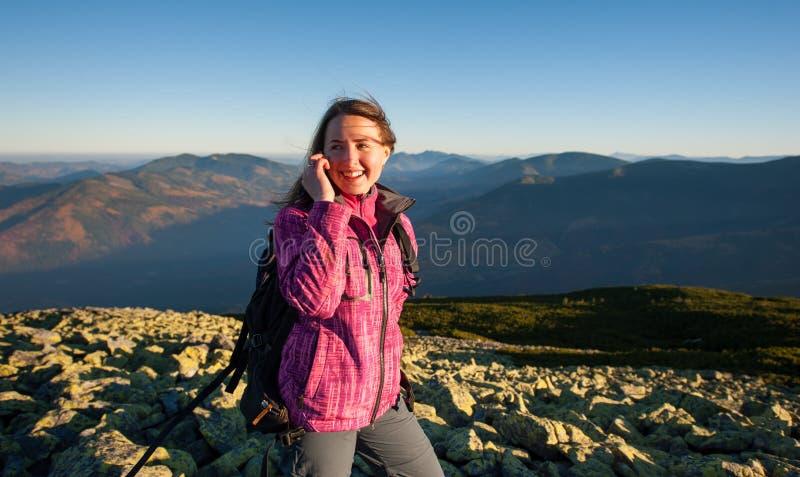 年轻逗人喜爱的女性背包徒步旅行者谈的手机画象  库存照片