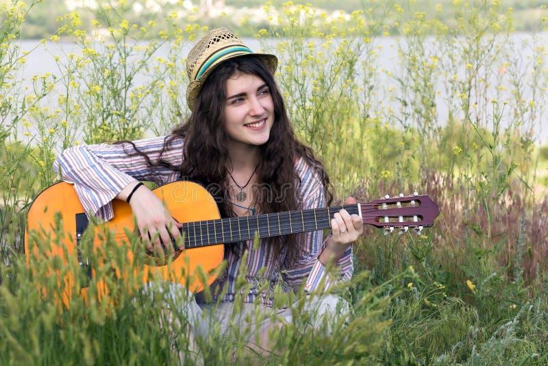 逗人喜爱的女性音乐家坐绿草 图库摄影