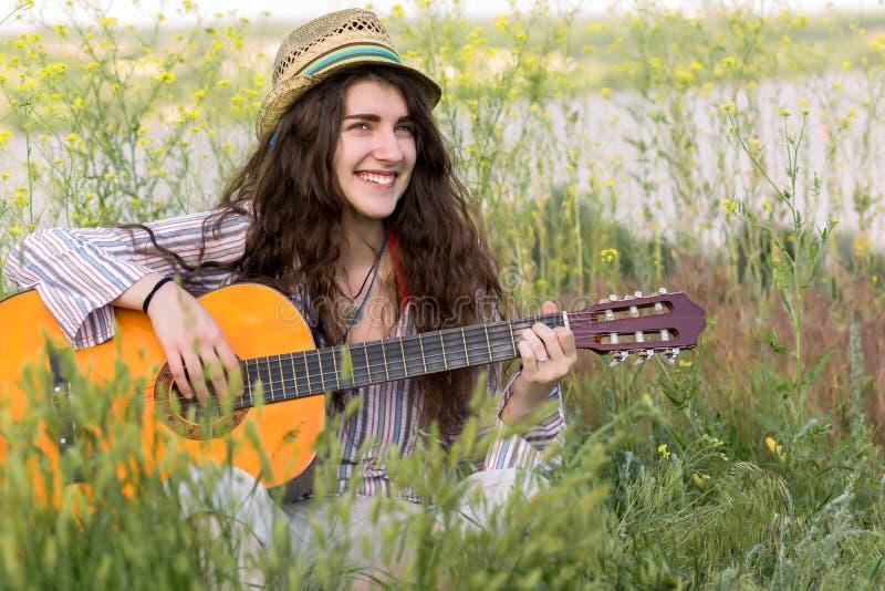 逗人喜爱的女性音乐家坐绿草 库存图片