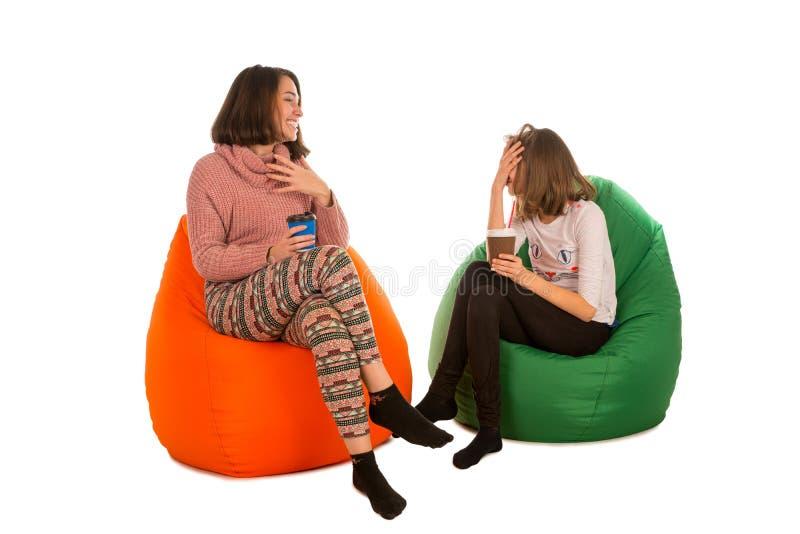 年轻逗人喜爱的妇女和笑的女孩坐装豆子小布袋椅子和 免版税图库摄影