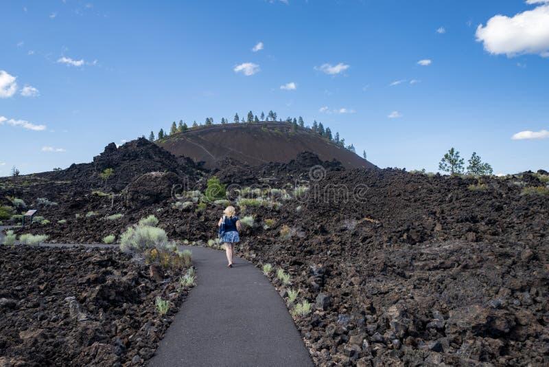 逗人喜爱的妇女在俄勒冈采取沿溶解的土地足迹的一次远足熔岩土地纽贝里火山国家历史文物的 免版税图库摄影